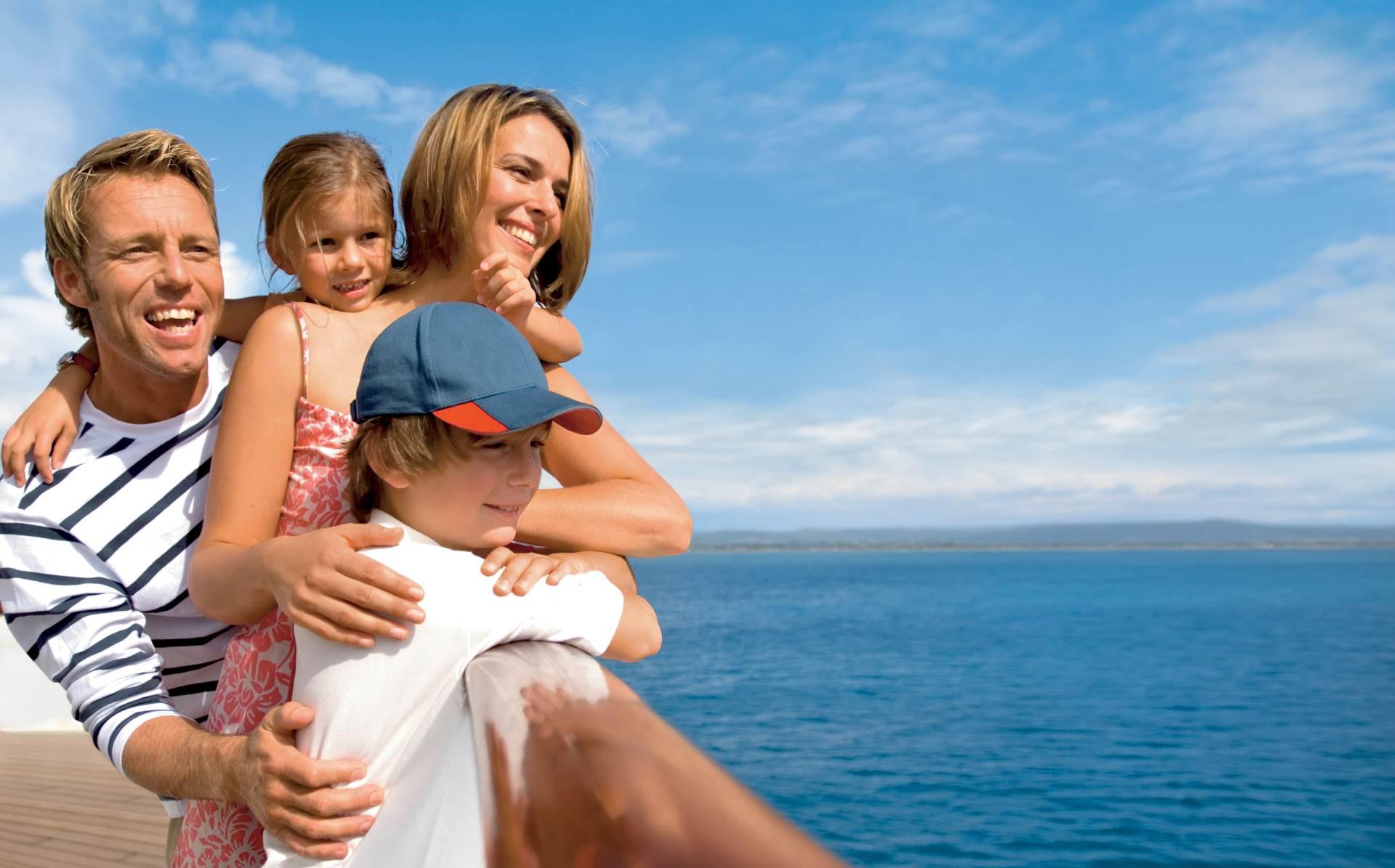 Familie an der Reeling eines Kreuzfahrtschiffs