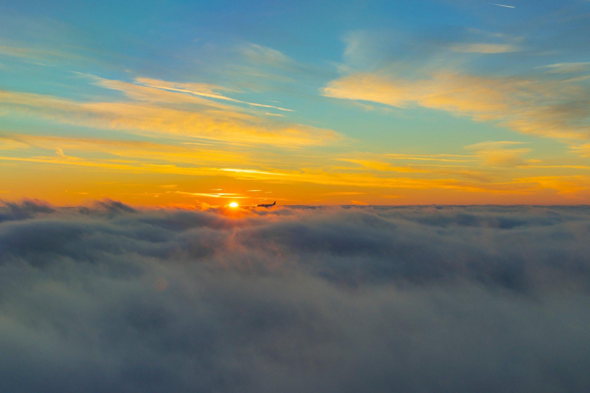 Flugzeug bei Sonnenaufgang über den Wolken