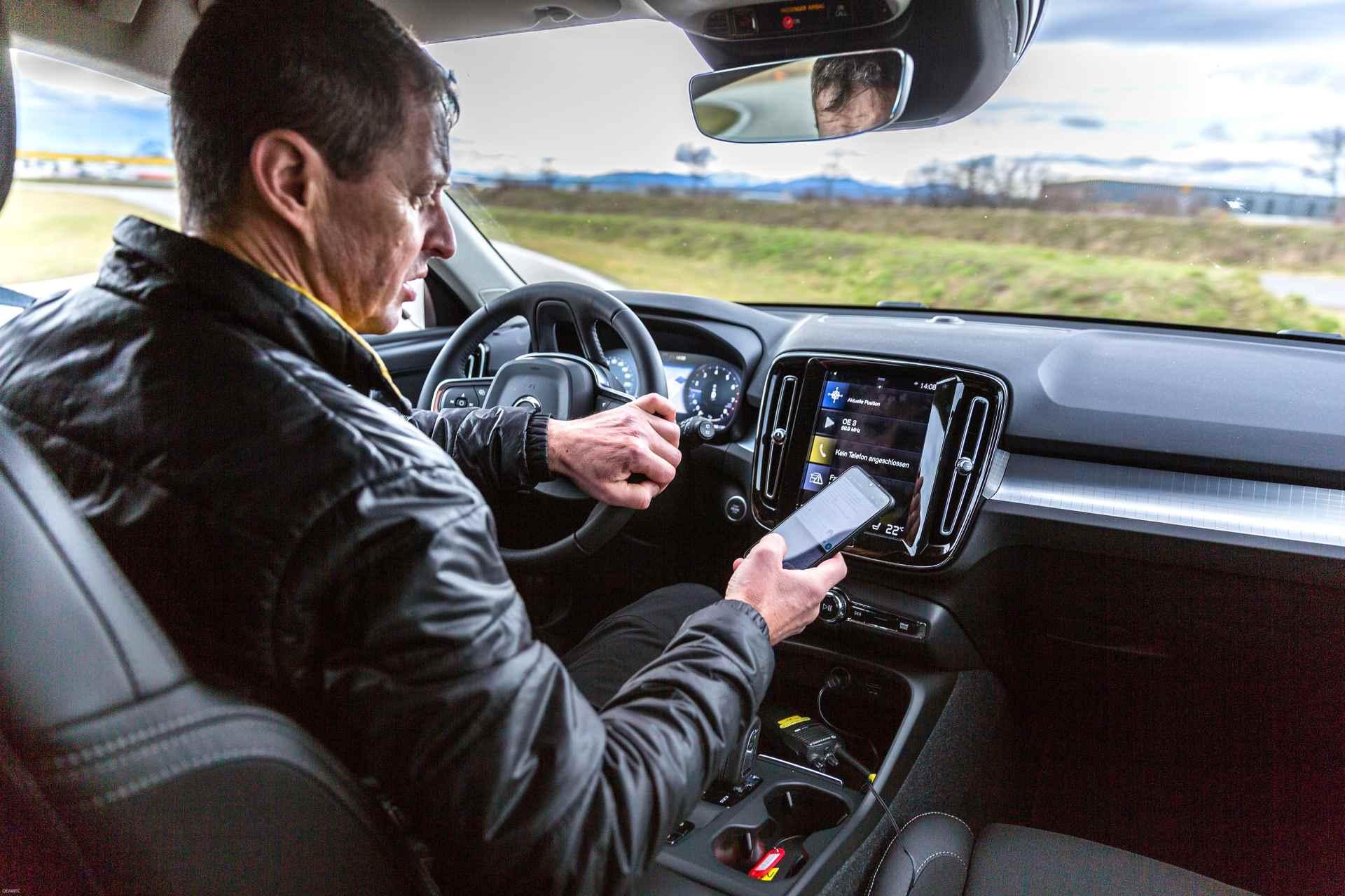 Autofahrer liest Nachricht auf Smartphone