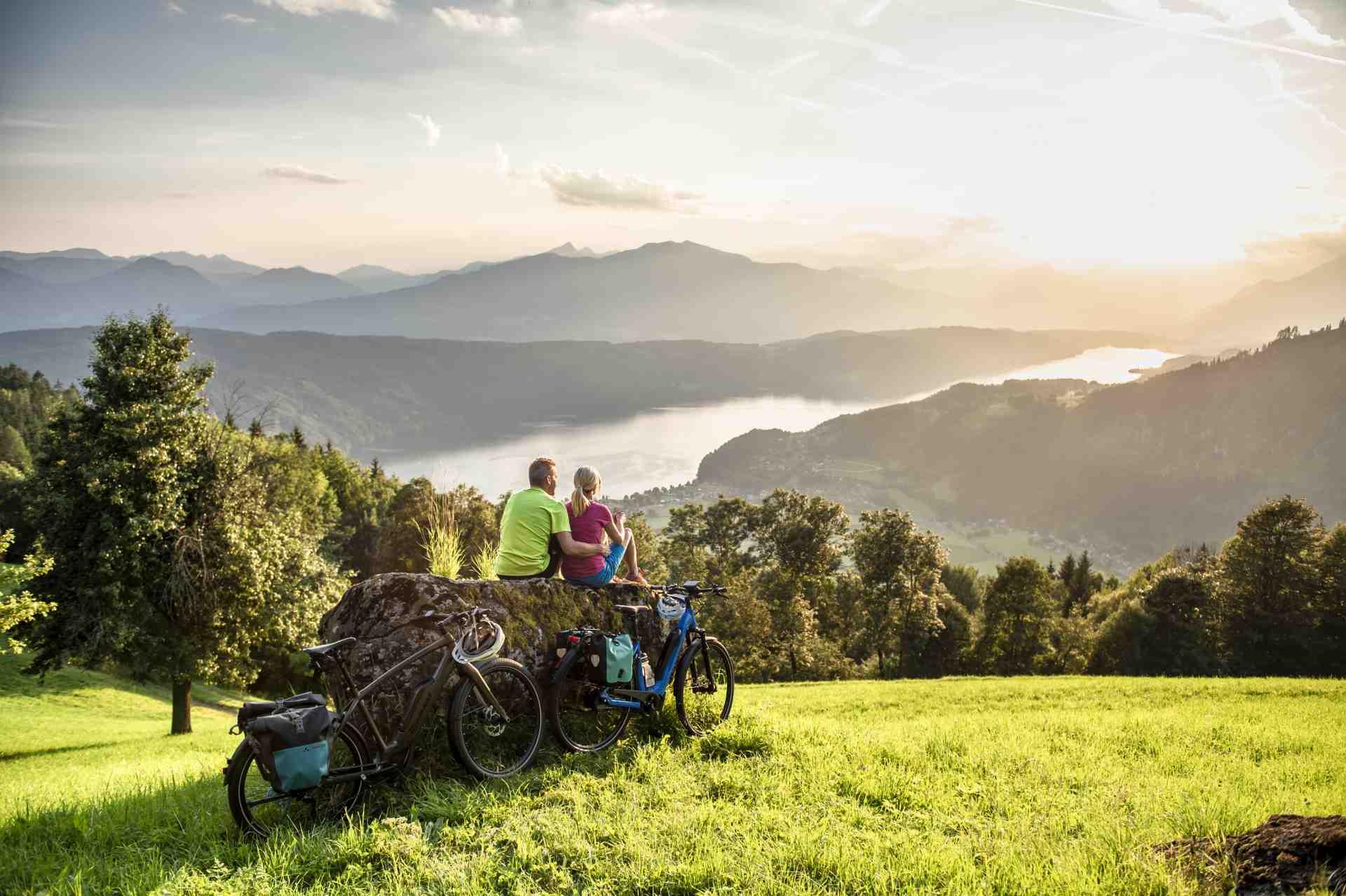 Fahrradfahrer blicken auf den Millstätter See bei Sonnenuntergang
