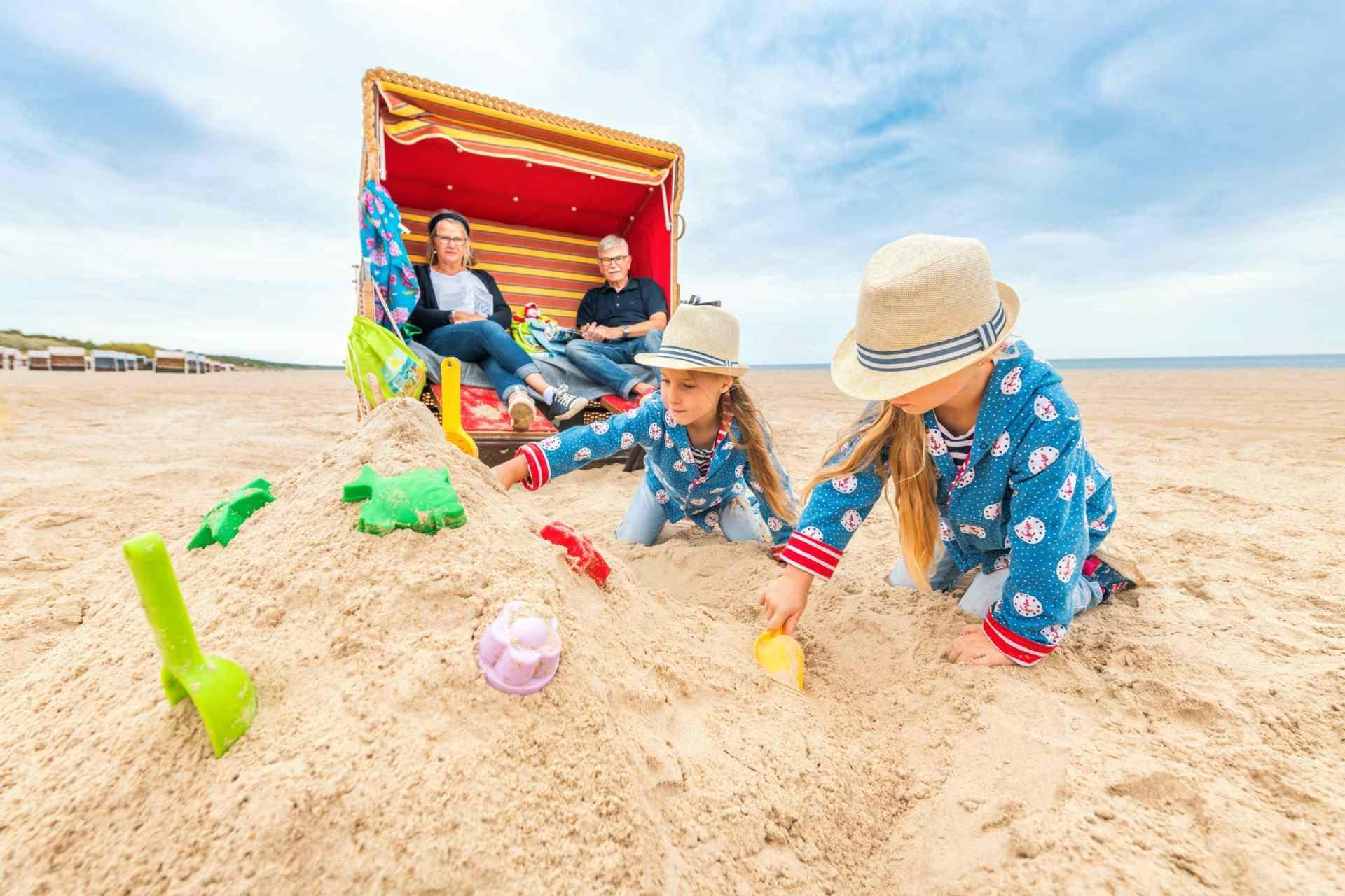 Kinder bauen Sandburgen vor einem Strandkorb in Trassenheide