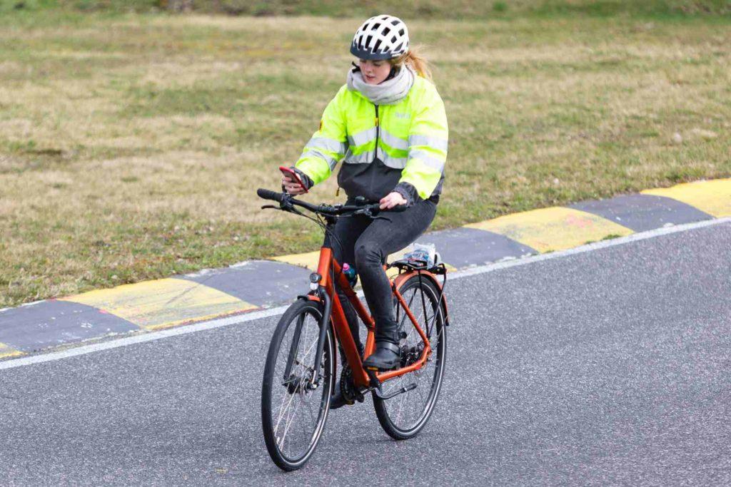 Radfahrerin mit Blick auf das Handy während der Fahrt